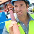 Worker lifting prop on construction site - Stock Photo