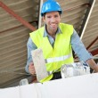 Bricklayer at work on construction site - Stock Photo