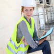 Woman engineer standing on building site - Stock fotografie