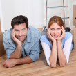 Couple laying on new house floor  — Stock Photo
