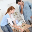 Stock Photo: Couple choosing wallpaper color for new house
