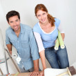 Couple putting new wallpaper in room - Foto Stock