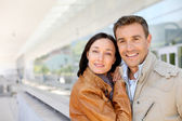 Smiling couple standing outside the airport — Stock Photo