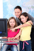 Teacher with kids in front of desktop computer — Stock Photo