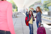 School girls waving goodbye at their mother — Stock Photo
