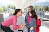 Mother giving kiss goodbye to children — Stock Photo