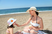 Mother putting sunscreen on her daughter's face — Stock Photo
