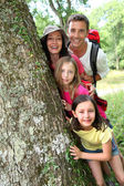 Portrait of happy family standing by a tree — Stockfoto