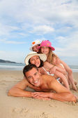 Portrait of family laying down sandy beach — Stock Photo