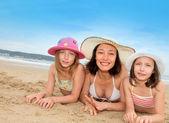 Matki i córki, leżąc na plaży — Zdjęcie stockowe