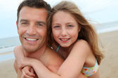Portrait of man with daughter on his back — Stock Photo
