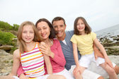 Happy family sitting by beach at low tide — Stock Photo
