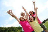 Cheerful family lifting arms up in the air — Foto Stock