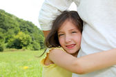 Little girl putting her arms around her father waist — Stock Photo