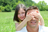 Young girl hiding her father eyes — Stock Photo