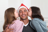 Girls kissing their father on Christmas day — Stock Photo