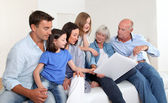 3-generation family looking at photo album — Foto de Stock