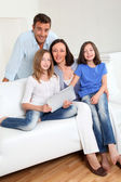 Parents and children using electronic tablet at home — Stock Photo