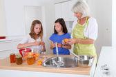 старший женщина, делая абрикосовое варенье с грандкидс — Стоковое фото