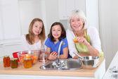 Senior woman making apricot jam with grandkids — Stock Photo