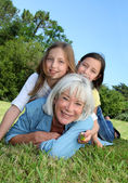 Starší žena vleže v parku s holkama na zádech — Stock fotografie