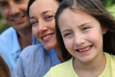 Portrait of smiling little girl with parents — Stock Photo