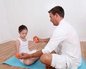 Man helping young girl with fitness exercises — Stock Photo