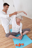 Sport coach training senior woman with stretching exercises — Stock Photo