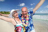 Happy senior couple at tropical beach — Stock Photo