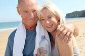 Portrait of athletic senior couple on the beach — Stock Photo