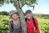 Portrait of happy senior couple hiking in natural landscape — Stock Photo