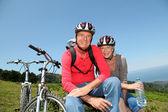 Senior couple riding mountain bikes in natural landscape — Stock Photo