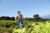 Senior woman riding mountain bike — Stock Photo