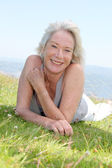 Portrait of cheerful senior woman in natural landscape — Stock Photo