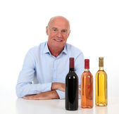 Portrait of winemaker with bottles of wine — Stock Photo
