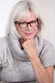Portrait of smiling senior woman with eyeglasses — Stock Photo