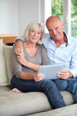 Senior couple using electronic tablet at home — Stock Photo