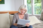 Porrtait of senior woman using electronic tablet at home — Stock Photo