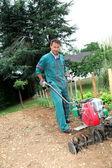 Gardener using motorized cultivator — Stok fotoğraf