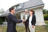 Real-estate agent with senior couple buying new house — Stock Photo