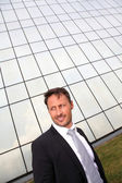 Portrait of businessman standing in front of modern building — Stock Photo