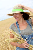 Beautiful woman with straw hat standing in wheat field — Stock Photo