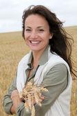 Beautiful woman standing in wheat field — Stock Photo