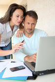 Couple working at home on laptop computer — Stock Photo