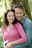 Portrait of smiling couple in forest — Stock Photo