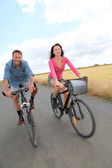 Couple riding bicycle on country road — Stock Photo