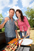 Happy couple cooking meat on barbecue grill — Stock Photo