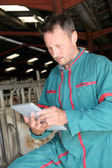 Farmer in barn using electronic tablet — Stock Photo