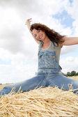 Woman having fun sitting on hay bale — Stock Photo