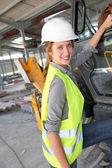Construction worker climbing on machine — Stock Photo